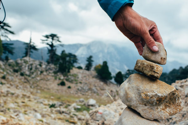 male hand sets a pointer out of stones - Cairn. Marking the way in the hike